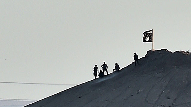 IS militants place flag atop hill in Kobani (Photo: AFP)