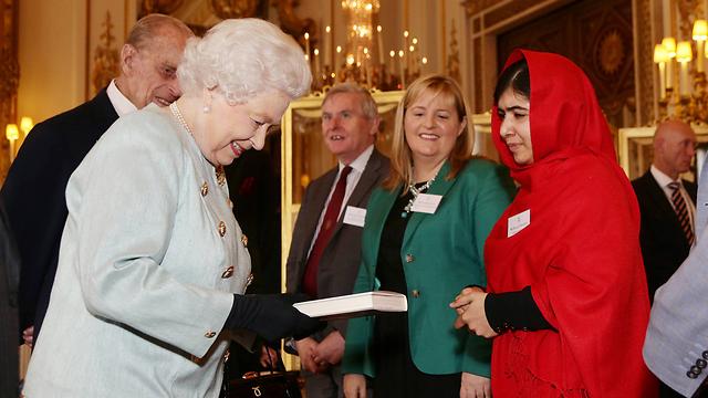 מעניקה את הספר למלכת בריטניה אליזבת (צילום: gettyimages) (צילום: gettyimages)