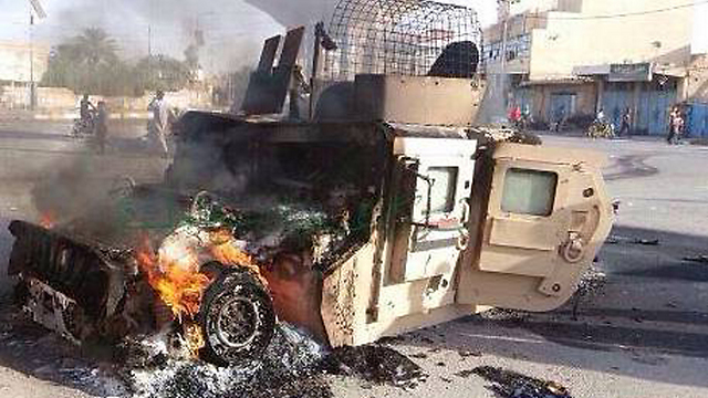 Iraqi military vehicle set on fire by ISIS militants in Hit, Anbar province (Photo: AP)