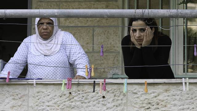 Two Palestinian women stand at their balcony over looking the entrance of the neighboring house that belongs to Palestinian Ziad Qarain, which Jewish settlers moved into (Photo: AP)