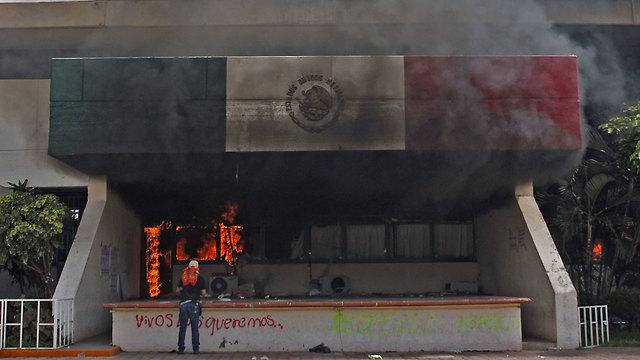 רעולי פנים הציתו את בניין העירייה באיגואלה (צילום: AFP) (צילום: AFP)