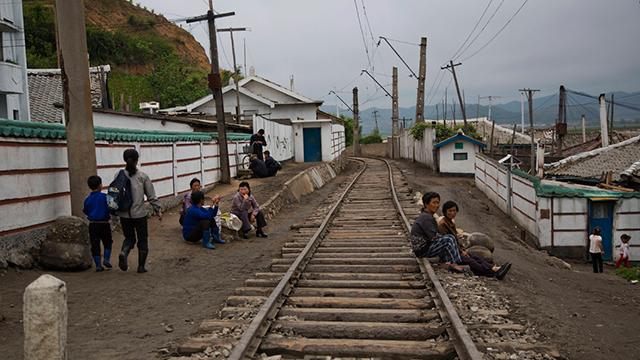 תושבים נחים לצד מסילת רכב בכפר במחוז האמגיונג (צילום: AP)