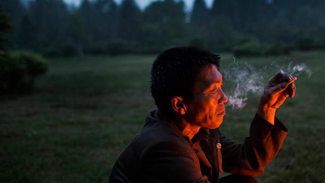 צפון קוריאני בסאמג'יון מעשן סיגריה ליד מדורה שבה הוא צולה עוף ותפוחי אדמה (צילום: AP)