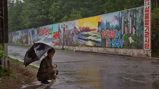 תושב צפון קוריאני תופס מחסה מהגשם על רקע כרזות תעמולה בסאמג'יון (צילום: AP)