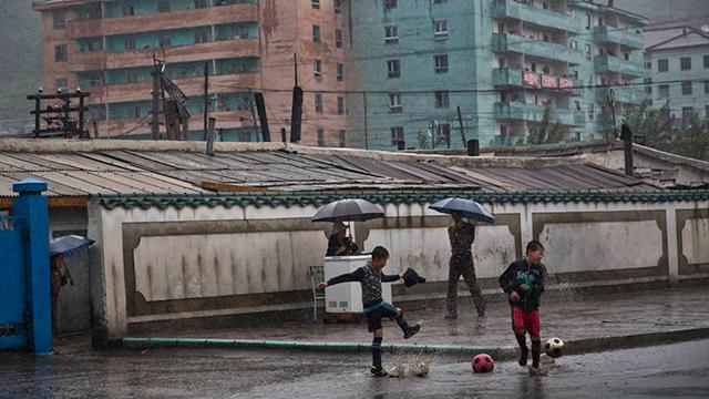 כדורגל ומטריות בגשם שוטף בהייסאן (צילום: AP)