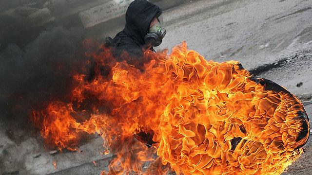 Palestinian throws burning tire in Kalandia a week before (Photo: AP)