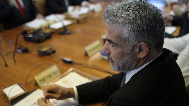 Lapid at government meeting (Photo: Alex Kulmonyski)