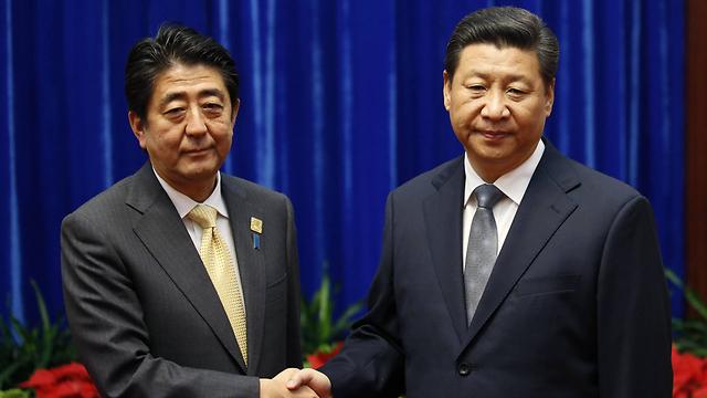 לחיצת היד ביניהם העלתה תקוות להתחממות היחסים בין סין ליפן. שי ואבה (צילום: gettyimages)