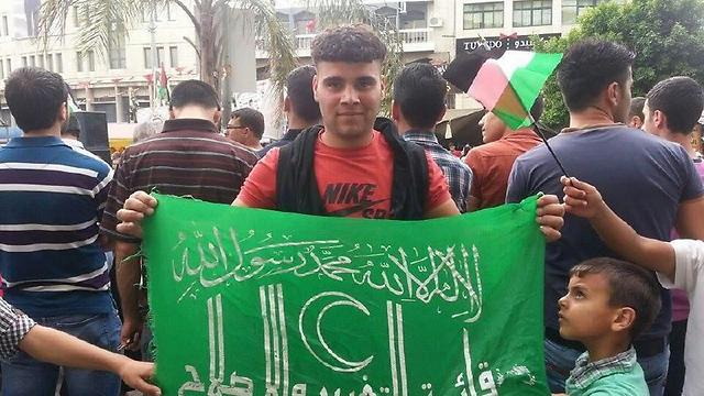 נור א-דין חואשיה עם דגל המפלגה שחמאס שהריצה לבחירות ()