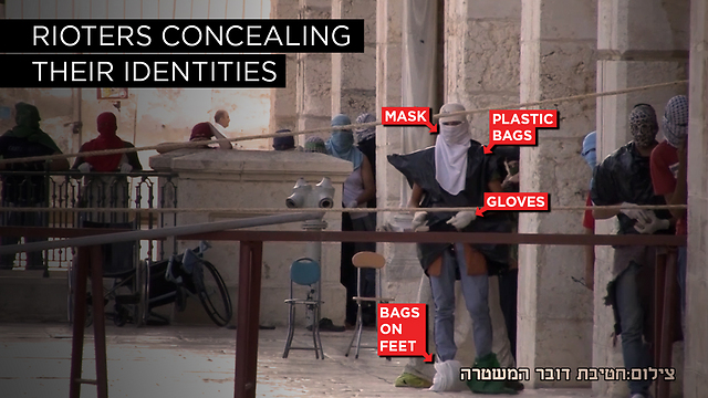 Palestinians are shown wearing plastic bags and gloves while rioting from within al-Aqsa mosque. (Photo: Israel Police) (Photo: Israel Police)