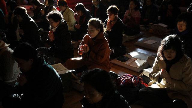 הורים מתפללים למען הצלחת ילדיהם בכנסייה סמוכה למקום המבחן (צילום: Getty Images  )