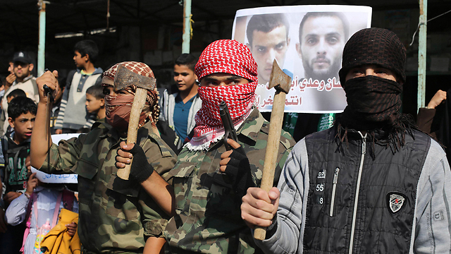 Youths in Gaza pose with axes while celebrating attack (Photo: Reuters)