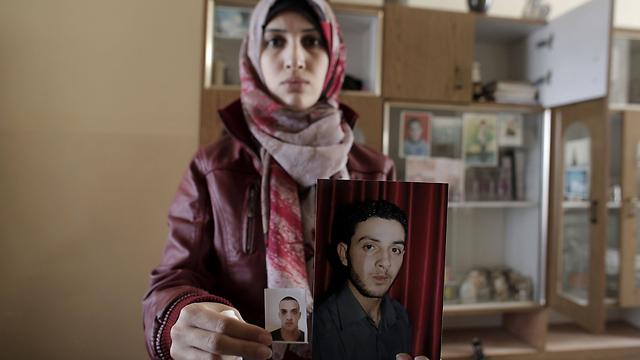 קרובת אחד המחבלים עם תמונותיהם (צילום: AFP) (צילום: AFP)