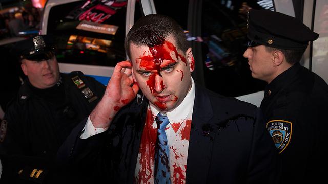 נוזל אדום הותז על שוטר  (צילום: AP) (צילום: AP)