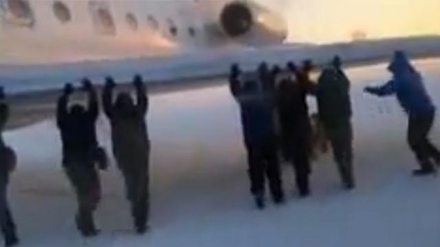 עברו על הנהלים? הנוסעים דוחפים את המטוס (צילום: מתוך יוטיוב) (צילום: מתוך יוטיוב)
