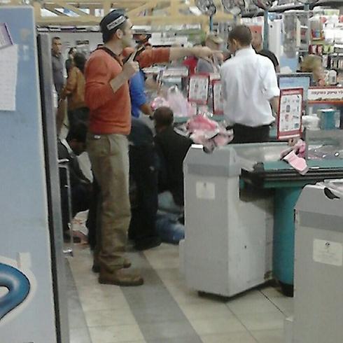 The attacker being subdued. (Photo: Shmuel Burnstein)