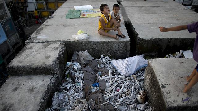 ילדים שחיים בבית קברות משחקים ליד עצמות אדם במנילה, הפיליפינים. צילום: נואל סליס (צילום: AFP) (צילום: AFP)