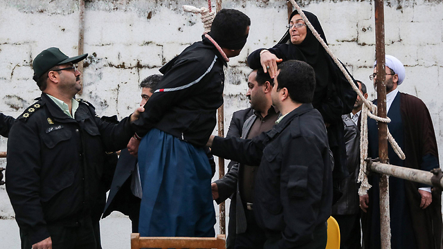 איראן: אמו של עבדאללה חוסיין זאדה, שנרצח לפני מספר שנים ברחוב, סוטרת לרוצח בנה אך מוחלת לו ומודיעה כי החליטה לחון אותו. רגע לפני תלייתו למוות - הוא שוחרר. צילום: אראש חמושי (צילום: AFP) (צילום: AFP)