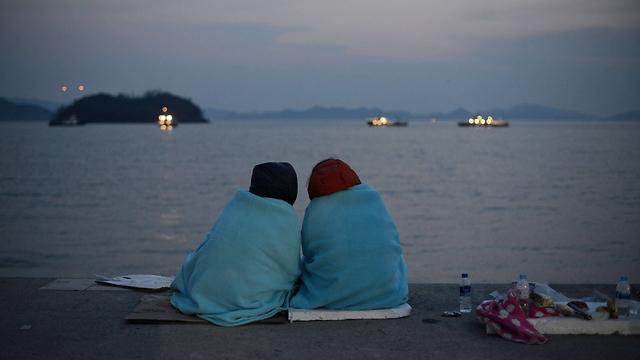 אולי הם יחזרו. קרובי קורבנות של אסון ספינת הילדים בדרום קוריאה מחכים על החוף (צילום: AFP) (צילום: AFP)