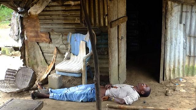 חולה אבולה מחוסר הכרה בליבריה. צילום: דומיניק פאגט (צילום: AFP) (צילום: AFP)