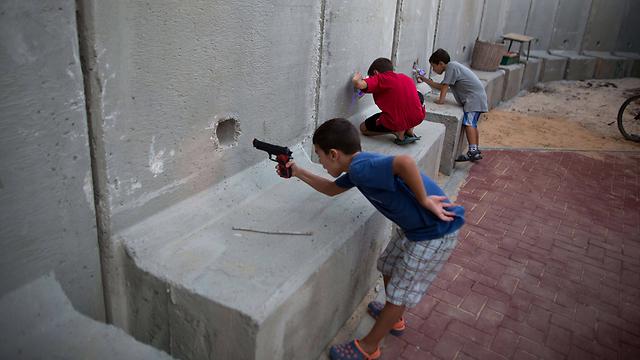 ילדים ישראלים משחקים באקדחי צעצוע מאחורי חומת מגן שהוצבה בנחל עוז. צילום: מנחם כהנא (צילום: AFP) (צילום: AFP)