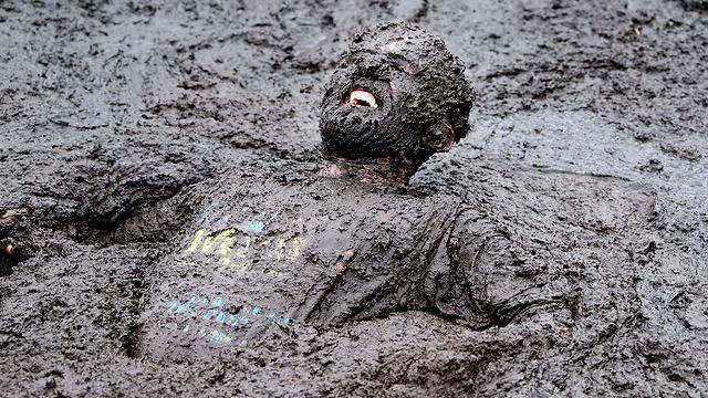 מתמודד במרוץ מכשולים בבוץ בצפון אירלנד. צילום: פול פיית' (צילום: AFP) (צילום: AFP)