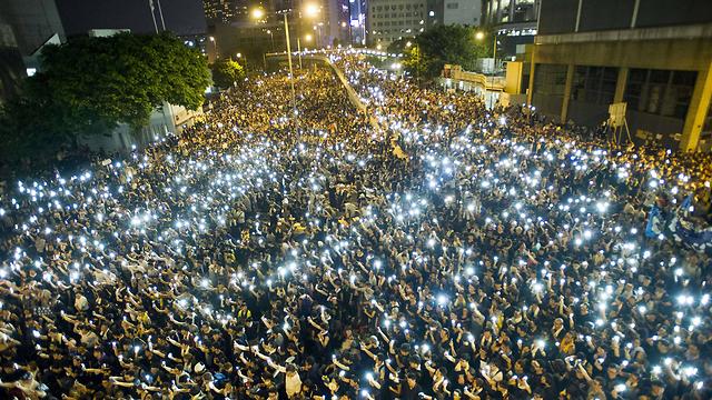 מפגינים מנופפים בטלפונים שלהם בהונג קונג. צילום: צ'אומה אולרוס (צילום: AFP) (צילום: AFP)