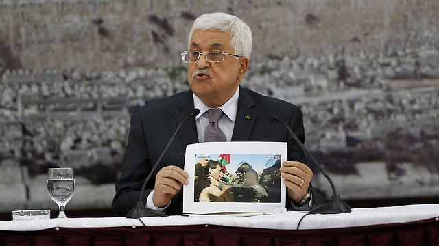 Abbas holding picture of Abu Ein during confrontation (Photo: Reuters) (Photo: Reuters)