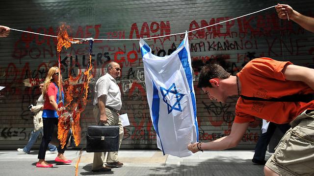 מפגין מצית דגל ישראל באתונה (צילום: AP) (צילום: AP)