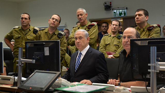 Then-IDF chief Gantz (standing in the middle), Prime Minister Netanyahu and then-defense minister Ya'alon (both seated) at the Kirya IDF headquarters during Operation Protective Edge (Photo: GPO)