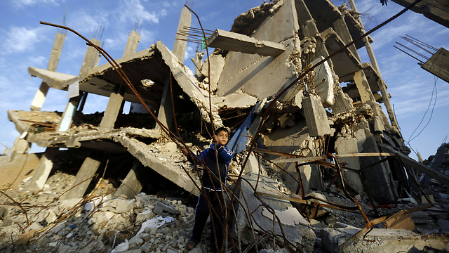 Palestinian boy playing outside building destroyed in summer Gaza war (Photo: AFP) (Photo: AFP)