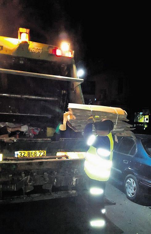 עובד התברואה משליכים קרטונים למשאיות האשפה הרטובה (צילום: תומי הרפז)