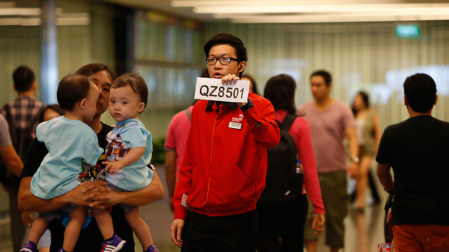 Airport worker in Singapore locates family members of those on board missing AirAsia plane. (Photo: Reuters) (Photo: Reuters)