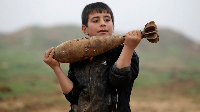 Child holds mortar in Idlib, Syria (Photo: Reuters)