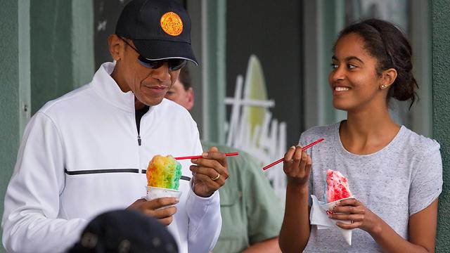 """ארה""""ב משפיעה על מדינות אחרת לא באמצעות כוח וכפייה, אלא באמצעות המשיכה של ערכיה והיותה מודל לחיקוי. אובמה ובתו מליה נהנים מגלידה בהוואי (צילום: AP)"""