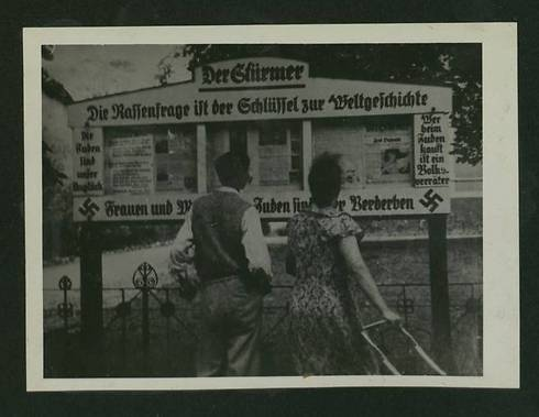 Those buying from Jews are betraying the country, written next to a notice board (Photo courtesy of the National Library)