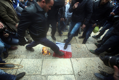 Palestinians stomp on French flag near Al-Aqsa mosque. (Photo: EPA)