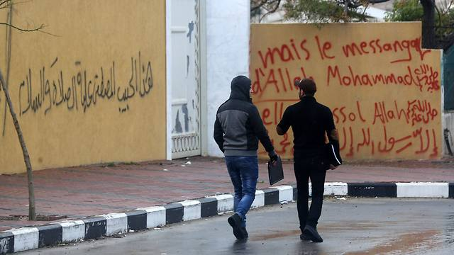Palestinians walk past walls of  French Cultural Center that were painted overnight with graffitti (Photo: AFP) (Photo: AFP)