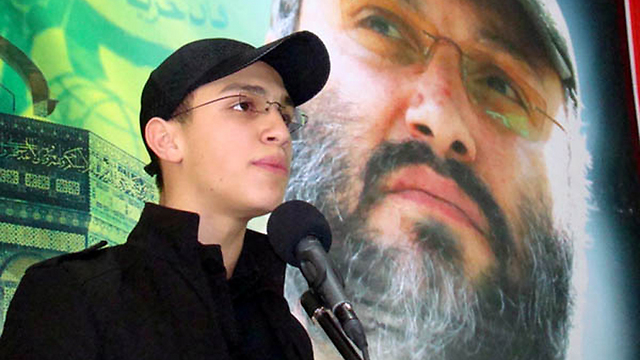Mughniyeh with an image of his father
