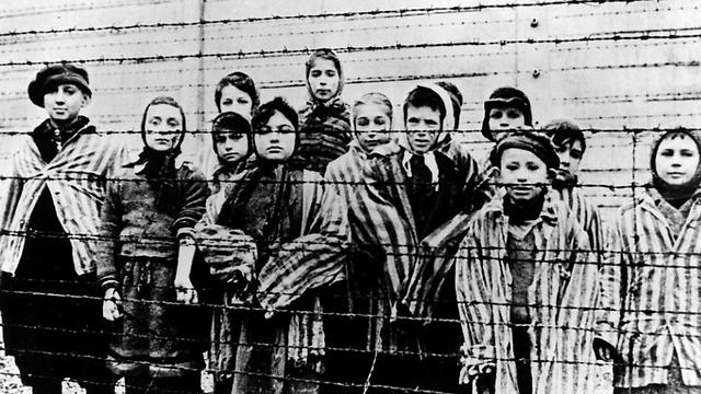 A picture taken just after the liberation by the Soviet army in January, 1945, shows a group of children wearing concentration camp uniforms behind barbed wire fencing in the Auschwitz Nazi concentration camp (Photo: AP) (Photo: AP)