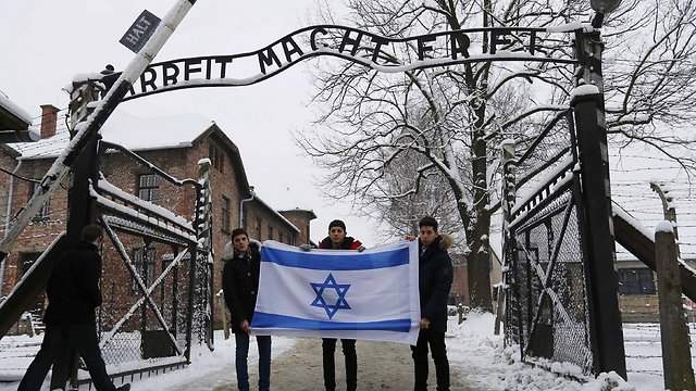 Visitors hold Israeli flag at entrance of Auschwitz (Photo: Reuters)