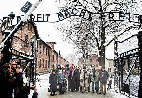 """הניצולים, מתחת לשלט """"העבודה משחררת"""" (צילום: MCT) (צילום: MCT)"""