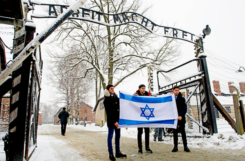 Teens holding the Israeli flag at the entrance to Auschwitz (Photo: MCT)