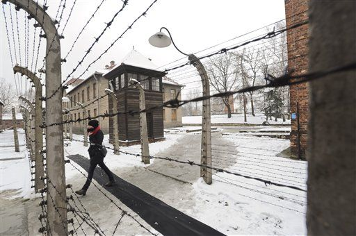 A visitor walks by barbed wire fences at the Auschwitz Nazi death camp in Oswiecim, Poland (Photo: Associated Press) (Photo: Associated Press)