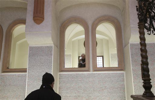 A tourist reads names of holocaust victims written on the walls of Pinkas Synagogue (Photo: Associated Press) (Photo: Associated Press)