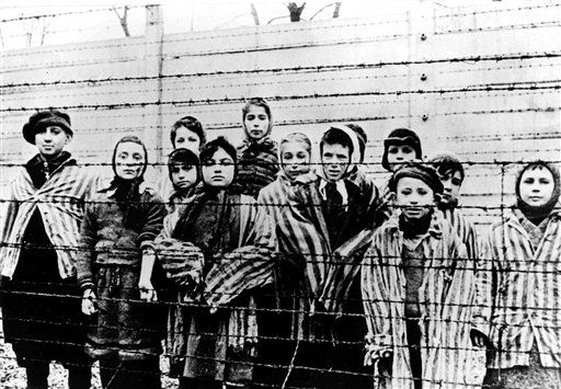 A picture taken after liberation by Soviet army in1945 shows children wearing concentration camp uniforms behind barbed wire fence in Auschwitz concentration camp (Photo: AP) (Photo: Associated Press)