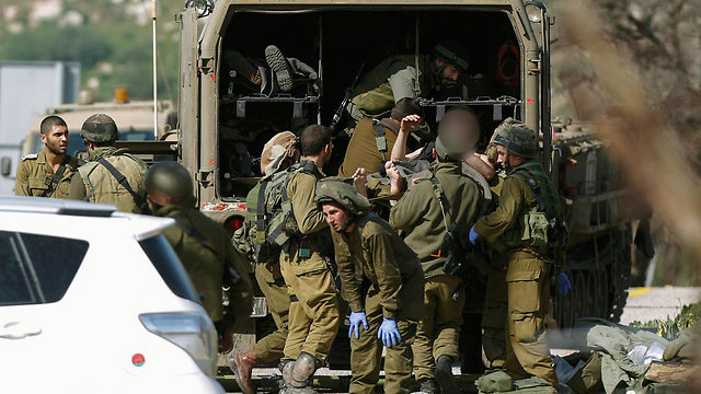 IDF soldiers evacuating wounded from scene of attack (Photo: EPA) (Photo: EPA)