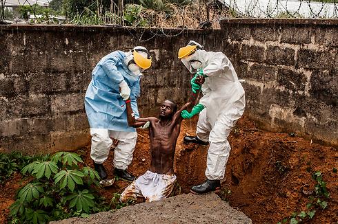 אנשי סיוע מחזירים לבידוד חולה אבולה שברח בסיירה ליאון (צילום: EPA) (צילום: EPA)