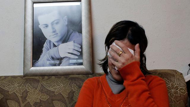 האם בוכה וברקע תמונת הבן (צילום: רויטרס) (צילום: רויטרס)