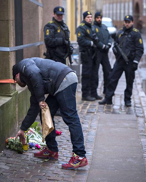 מניחים זרים ליד בית הכנסת בקופנהגן (צילום: AFP) (צילום: AFP)